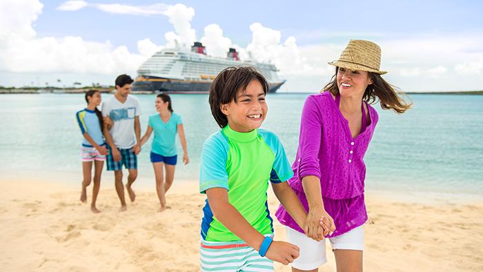 Uma família de cinco pessoas caminha na areia na Disney Castaway Cay com um navio da Disney Cruise Line atracado ao fundo