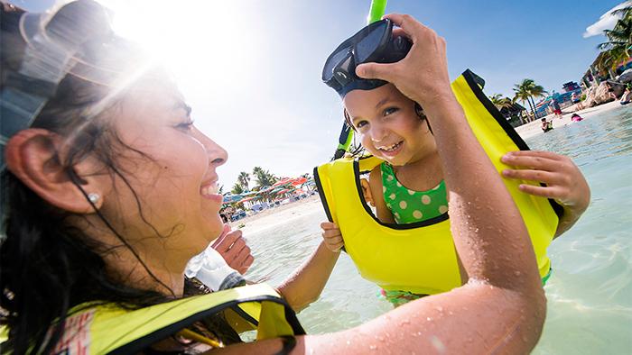 Una mamá ajusta el visor con snorkel de su hija antes de nadar