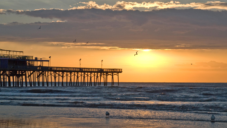 Uma praia ao nascer do sol com um píer, gaivotas, ondas e nuvens no céu