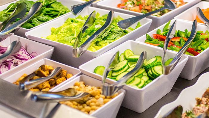 Um bufê de saladas que oferece alface, espinafre, pimentões, pepino e seletas de legumes
