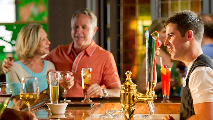 Casal saboreia drinks em um bar enquanto um bartender observa