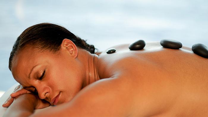 Uma mulher de olhos fechados relaxa deitada em uma maca durante um tratamento com pedras colocadas sobre as costas
