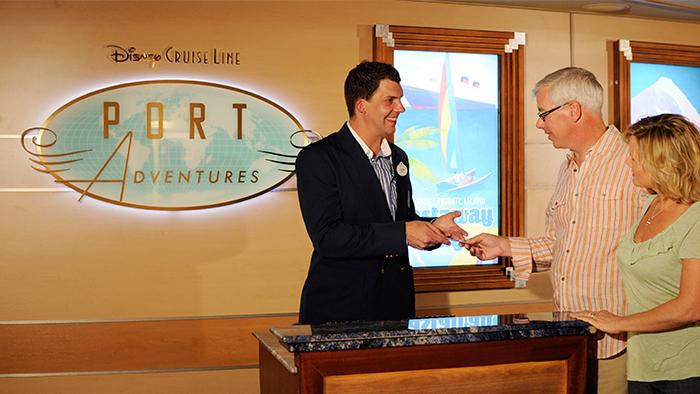 Dois hóspedes da Disney Cruise Line conversam com um tripulante da Disney no balcão de Aventuras Portuárias no navio