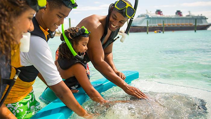 Una familia de cuatro con equipo de snorkel acarician una mantarraya en Disney Castaway Cay