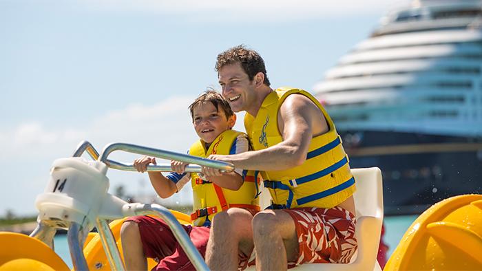 Un papá y su hijo montados en una bicicleta de agua con un barco de Disney Cruise Line anclado detrás de ellos