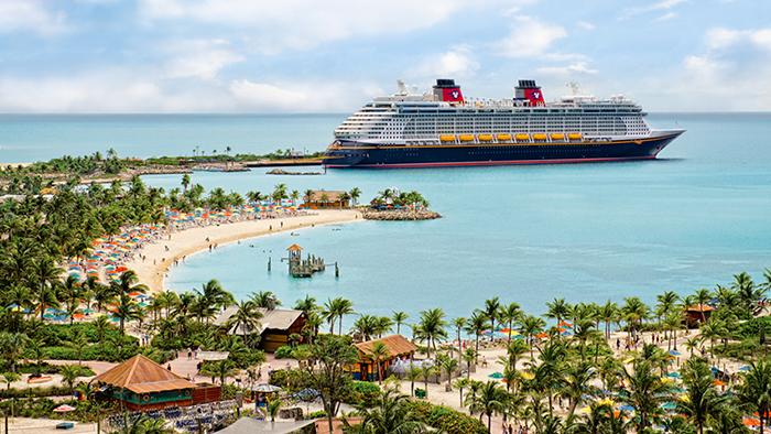 Tripulantes da Disney Cruise Line levam crianças de mãos dadas durante uma aventura portuária