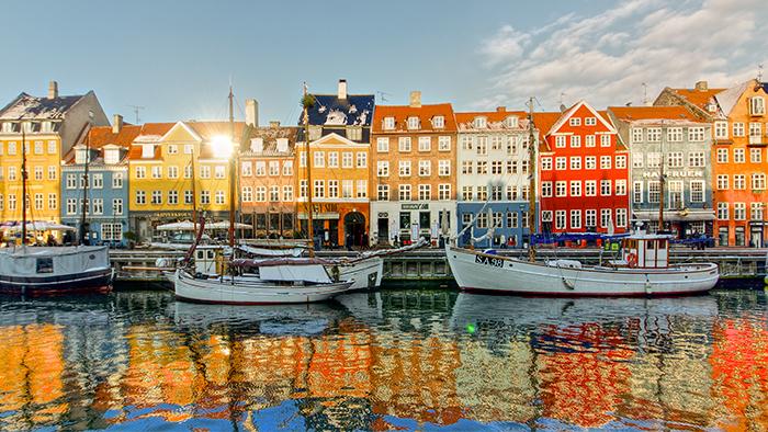 Uma fileira de casas margeando um porto repleto de barcos em Copenhague, na Dinamarca
