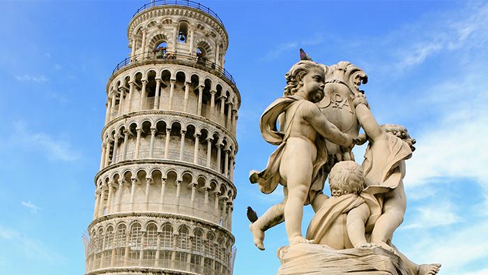 Una estatua de ángeles junto a la inclinada Torre de Pisa