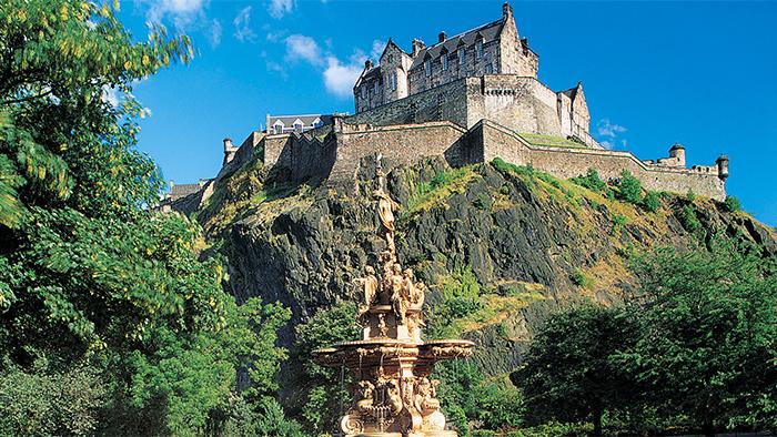 Una fuente y un castillo posados sobre una colina