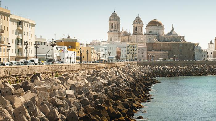 Bloques de concreto fortifican la costa junto a unos edificios antiguos en Cádiz, España
