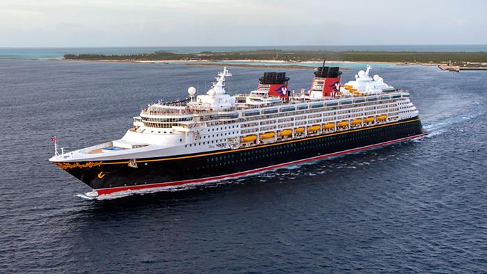 Um navio da Disney Cruise Line navega pelo oceano enquanto o sol começa a se pôr.