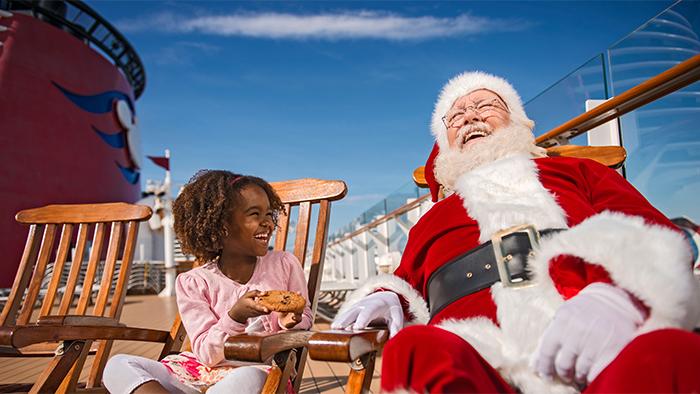 Uma menina oferece um biscoito a um sorridente Papai Noel no deck