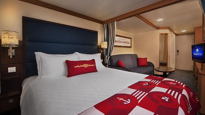 Cama com cobertor com estampa de tema náutico, sofá e mesa dentro de uma cabine de um navio da Disney Cruise Line