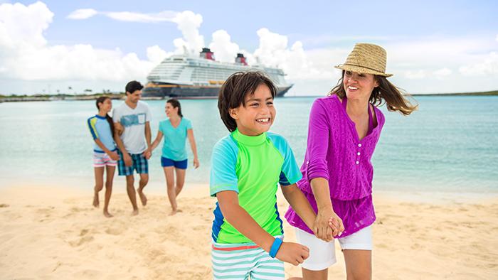 UUma família de cinco pessoas caminha na areia na Disney Castaway Cay com um navio da Disney Cruise Line atracado em segundo plano