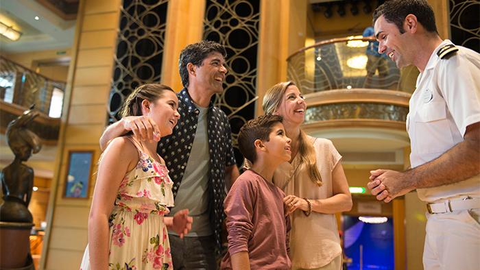 Uma família de quatro pessoas conversa com um tripulante da Disney Cruise Line no belo Atrium